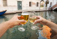Two glasses click toasting cheers of couple celebrating holidays. Two glasses of beer and wine, couple drinking by the canal in Venice romantic celebration of stock image