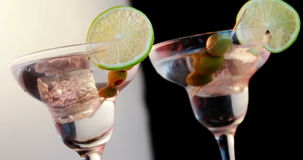Two glasses of cocktail garnished with lemon and olives. Close-up of two cocktail glasses garnished with lemon and olives stock footage