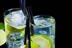 Two glasses with cocktail and ice with lime slice on black background Royalty Free Stock Image