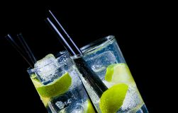 Two glasses with cocktail and ice with lime slice on black background with space for text Stock Images
