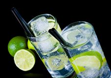 Two glasses with cocktail and ice with lime slice on black table Stock Photos
