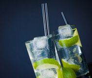 Two glasses with cocktail and ice with lime slice on dark blue background Royalty Free Stock Image
