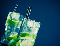 Two glasses with cocktail and ice with lime slice Royalty Free Stock Images