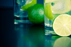 Two glasses with cocktail and ice with lime slice on table Royalty Free Stock Image