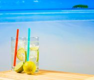 Two glasses of cocktail with lime slice on blur beach Royalty Free Stock Photo