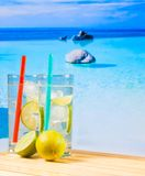 Two glasses of cocktail with lime slice on blur beach Royalty Free Stock Images