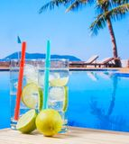 Two glasses of cocktail with lime slice near swimming pool Stock Photo