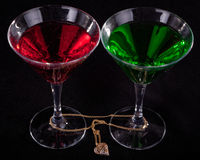 Two glasses of cocktails. And jewelry on a black background Stock Photography