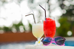 Two glasses of cocktails and sunglasses near pool Stock Photo