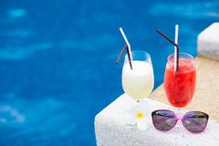 Two glasses of cocktails and sunglasses near pool Stock Photography