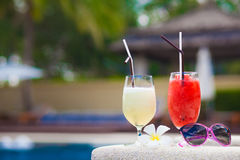 Two glasses of cocktails and sunglasses near pool Stock Photos