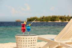 Two glasses with cocktails on table near beach bench or deck chair with blue ocean and white sand on background royalty free stock photo