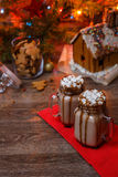 Two glasses of cocoa with marshmallows, whipped cream and chocolate syrup on wooden table and Gingerbread house, cookie Royalty Free Stock Photography