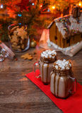 Two glasses of cocoa with marshmallows, whipped cream and chocolate syrup on wooden table and Gingerbread house, cookie Stock Image
