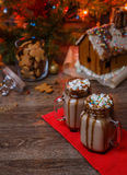 Two glasses of cocoa with marshmallows, whipped cream and chocolate syrup on wooden table and Gingerbread house, cookie Royalty Free Stock Image
