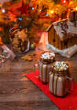 Two glasses of cocoa with marshmallows, whipped cream and chocolate syrup on wooden table and Gingerbread house, cookie Stock Images