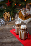 Two glasses of cocoa with marshmallows, whipped cream and chocolate syrup on wooden table and Gingerbread house, cookie Stock Photos