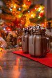 Two glasses of cocoa with whipped cream and chocolate syrup on wooden table and Gingerbread house, cookie jar and Royalty Free Stock Photo