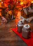 Two glasses of cocoa with whipped cream and chocolate syrup on wooden table and Gingerbread house, cookie jar and Stock Photo