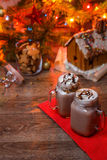 Two glasses of cocoa with whipped cream and chocolate syrup on wooden table and Gingerbread house, cookie jar and Royalty Free Stock Photos