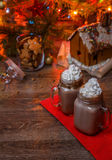 Two glasses of cocoa with whipped cream and chocolate syrup on wooden table and Gingerbread house, cookie jar and Stock Image