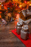 Two glasses of cocoa with whipped cream and chocolate syrup on wooden table and Gingerbread house, cookie jar and Royalty Free Stock Photography