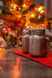 Two glasses of cocoa with whipped cream and chocolate syrup on wooden table and Gingerbread house, cookie jar and christmas tree w Stock Photo