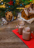 Two glasses of cocoa on wooden table and Gingerbread house, cookie jar and christmas tree with toys and garland on background. Royalty Free Stock Photography