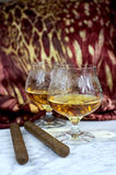 Two glasses of cognac with a cigar on a marble table Stock Photo