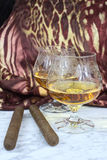Two glasses of cognac with a cigar on a marble table Stock Photography