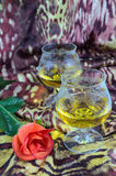 Two glasses of cognac with a red rose on a colored background Stock Images