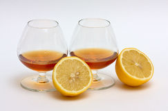 Two glasses of cognac and two halves of a lemon. On white background Stock Photo