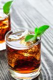 Two glasses of cola with ice and fresh mint on wooden table. Stock Photo