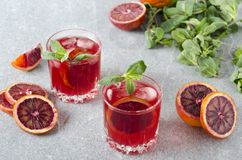 Two glasses of cold blood orange margarita, juicy mint on the grey bar surface royalty free stock image