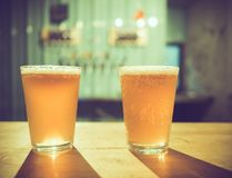 Two glasses of cold craft beer with white bubbles and shadow on wooden table at bar. Vintage dark tone, selective focus stock images