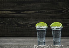Two glasses  cold silver tequila with lime on a black wooden bac Stock Photography
