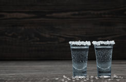 Two glasses of cold silver tequila in lime on a black wooden bac Stock Images