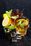 Two glasses with cold traditional iced tea with lemon, mint leaves and ice cubes. On wet black background royalty free stock photography