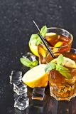 Two glasses with cold traditional iced tea with lemon, mint leaves and ice cubes. On wet black background stock photography