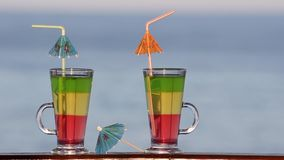 Two glasses with colored cocktails closeup on sea background stock video