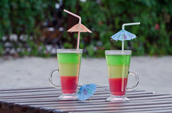 Two glasses with colored cocktails and straws on a wooden deck chair in the backyard Royalty Free Stock Image