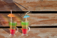 Two glasses with colored cocktails and straws on wooden planks Stock Image