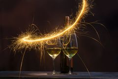 Two glasses containing wine with wine bottles are decorated with sparkling fireworks. Celebration and New years party concept royalty free stock photos