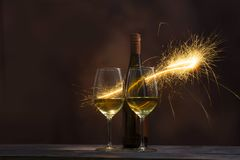 Two glasses containing wine with wine bottles are decorated with sparkling fireworks. Celebration concept photo stock photo