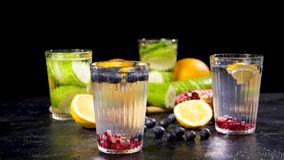 Two glasses with cucumber water and two with homemade lemonade. From berries, pomegranate and lemons. Black background stock video