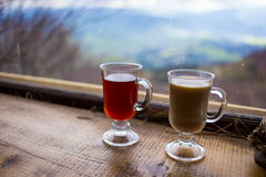 Two glasses,cup of red and milk hot drink.couple drinking hot co. Ffee and tea, coffee, tea, relax in the mountains, Carpathians,close-up Royalty Free Stock Image