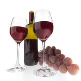 Two glasses with dark red wine on a white backgrou. Still life of two wine glasses, grapes and a bottle. Isolated on white background stock images