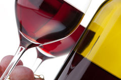 Two glasses with dark red wine on a white backgrou. Fragment of two glasses of red wine, grape clusters and bottles in the background stock photos