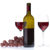 Two glasses with dark red wine on a white backgrou. Still life of two wine glasses, grapes and a bottle. Isolated on white background royalty free stock photos