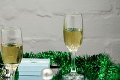 Two glasses of delicious champagne close up on a brown Christmas toy red, green, and gold color.  royalty free stock images